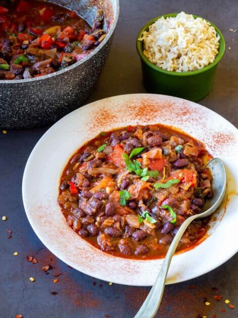 vegan chili served in white plate next to a pot