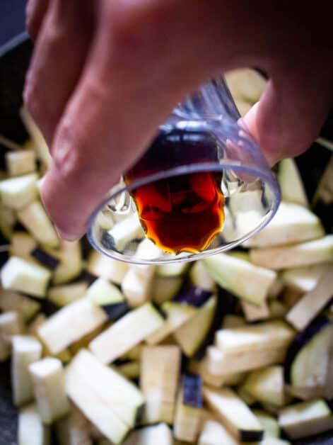 pouring soy sauce over eggplant cubes
