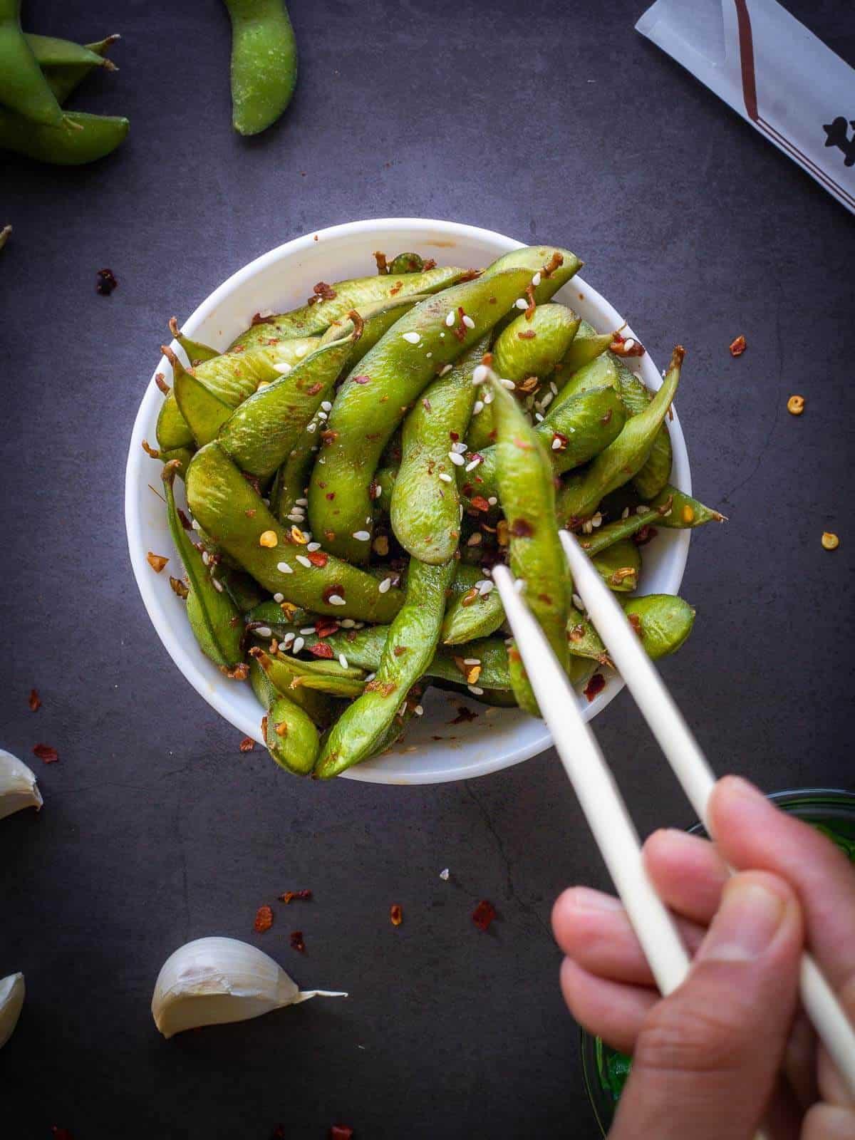 garlic edamame served with chopsticks