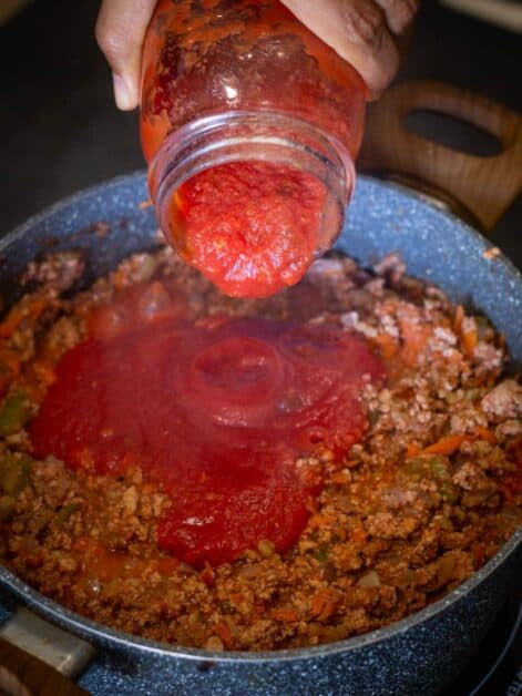 Vegetable Bolognese pouring tomato sauce