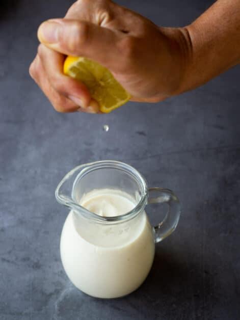 squeezing lemon on plant milk for homemade buttermilk