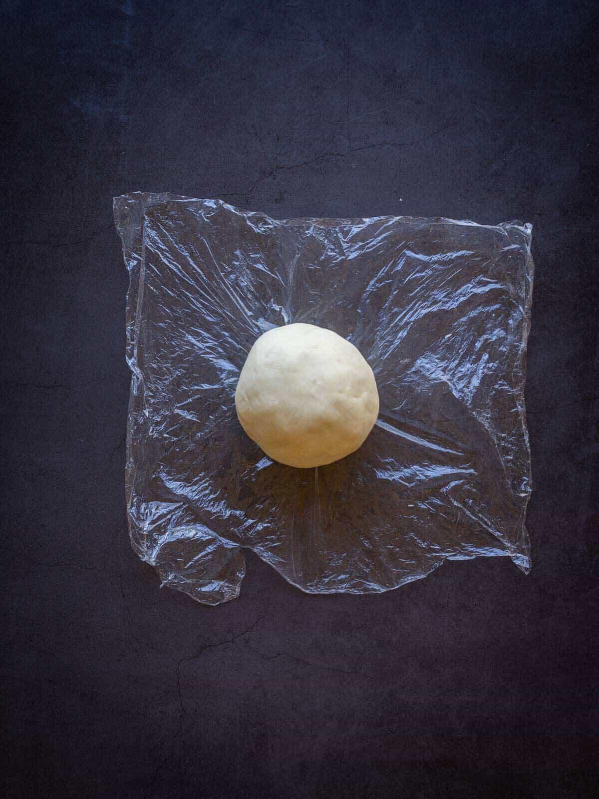 vegan no-roll-pie crust ball in plastic wrap