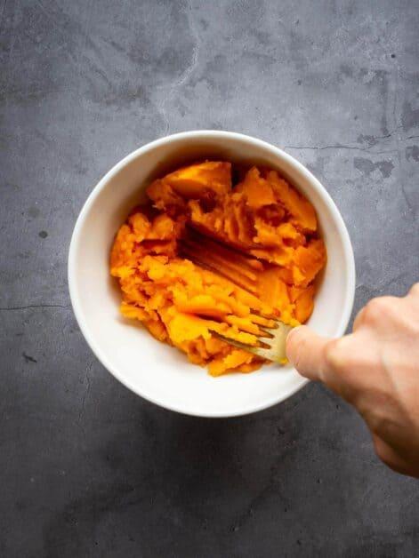 mashing pumpkin in saucepan