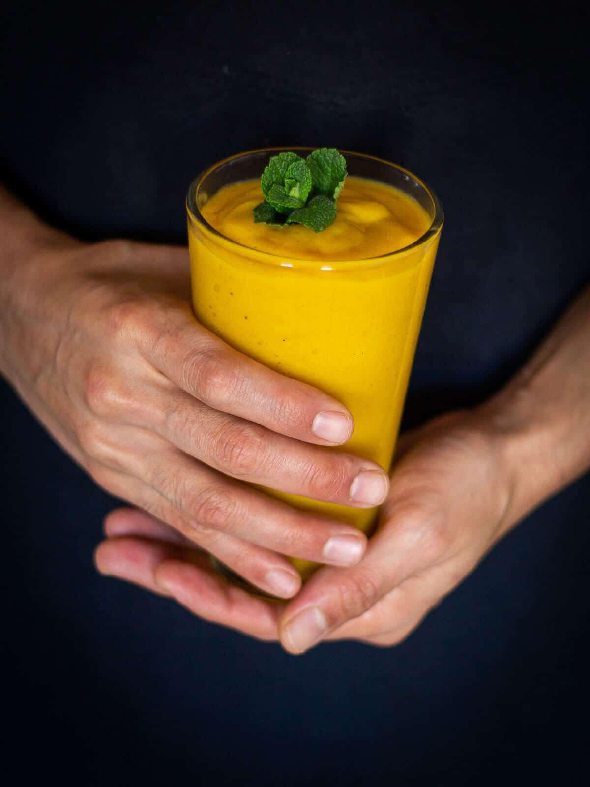 holding mango smoothie glass