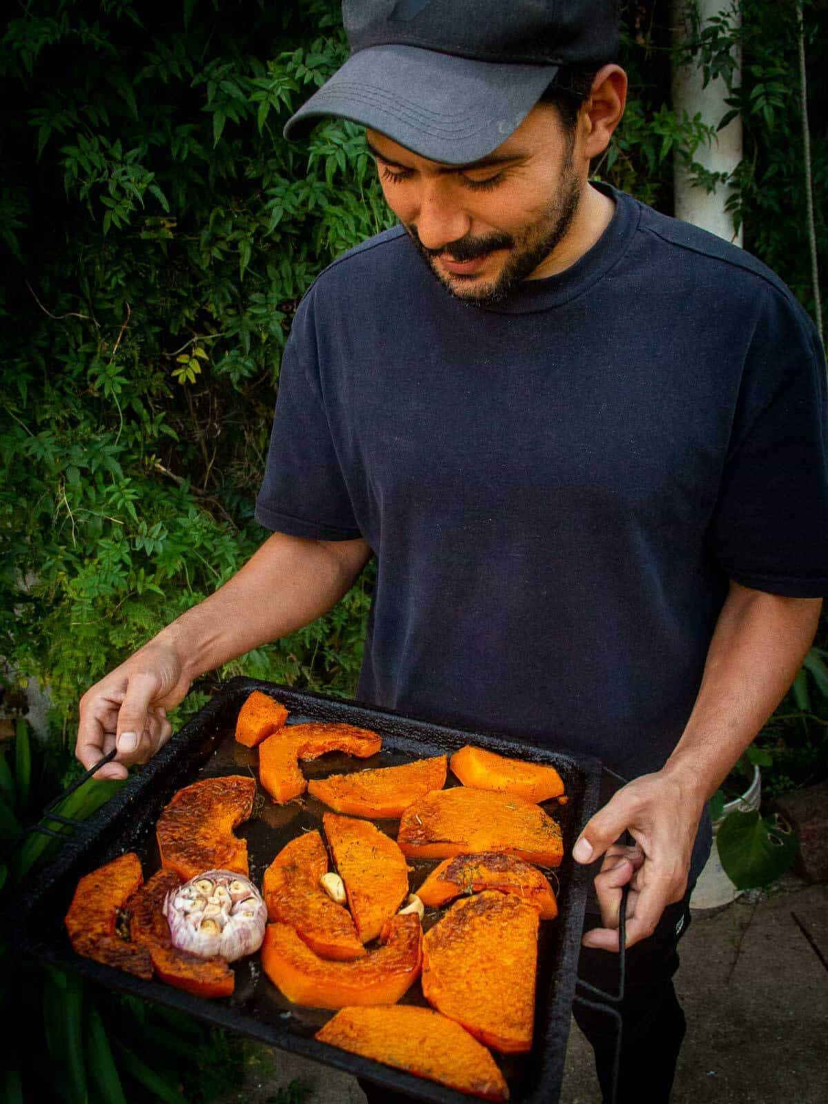 gus holding a roasted butternut squash tray