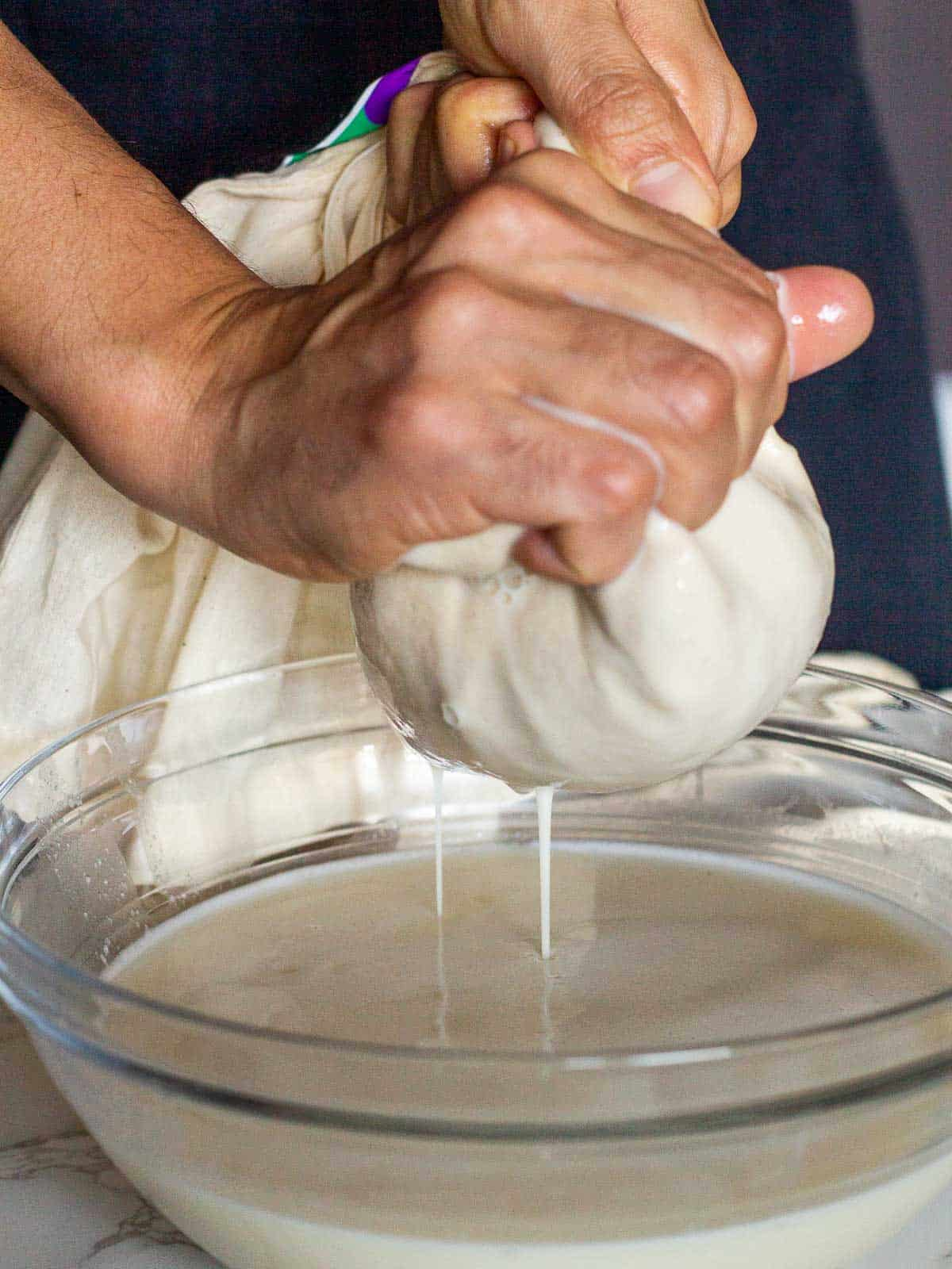 straining oat milk with hand